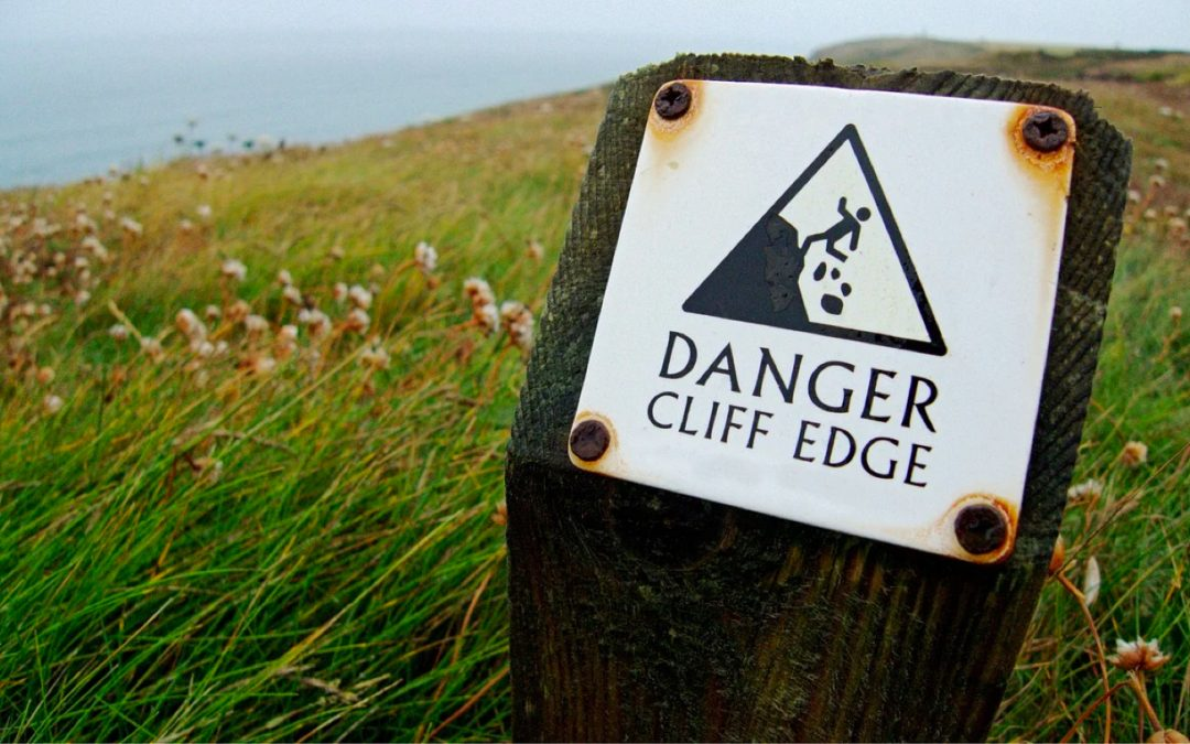 Danger: Cliff Edge sign in the grass by a cliff